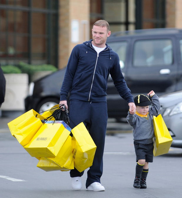 MANCHESTER UNITED STRIKER WAYNE ROONEY AND WIFE COLEEN SEEN GETTING WEIGHED DOWN WITH SELFRIDGES SHOPPING BAGS BUT GETS A HELPING HAND FROM HIS TODDLER SON KAI WHO'S SEE CARRYING HIS OWN SHOPPING WHILE MAKING THEIR WAY TO THE CAR.ONLY FOR USE IN REVEAL