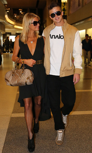 Paris Hilton and boyfriend River Viiperi seen arriving at LAX Airport for a flight. Before going through security they shop for sunglasses and earphones.