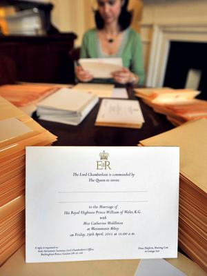 A member of the Lord Chamberlain's Office inserts invitations to the wedding of Prince William and Kate Middleton into envelopes