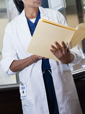 Model released - doctor reviewing medical record in hospital elevator, Cape Town, South Africa
