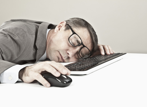 Stock image of man sleeping at desk