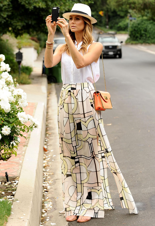 Stacy Keibler spotted taking candid shots on her iPhone 5 using the Duracell Powermat for extra battery life, 15 July 2013
