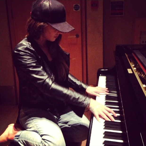 Cheryl Cole plays on a piano as she teases music comeback