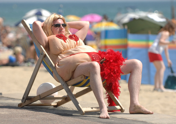 A groom in fancy dress makes the most of the sunny weather on Bournemouth beach during his stag do, July 2008