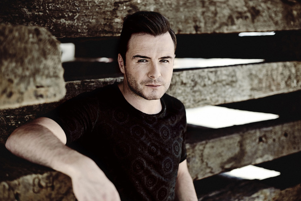 Shane Filan posed by a fenced area looking serious.