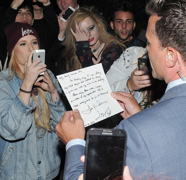 Lady Gaga personal security reading a note from Lady Gaga to the awaiting fans outside her hotel apologizing for not being able to go and meet them when returning to the hotel 29 Aug 2013