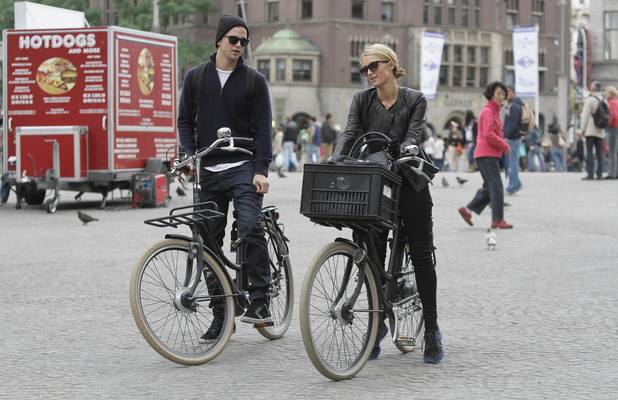 Paris Hilton pictured cycling around Amsterdam with her boyfriend River Viiperi. They visited the Pancake Bakery and also Dam Square. Sept 21 2013.
