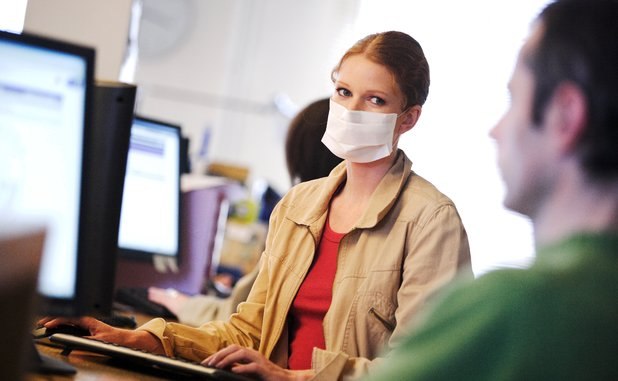 Model released - Woman at her workplace wearing a protective masque. Ill office worker.