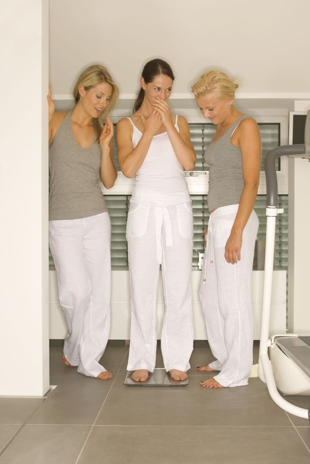 VARIOUS STOCK MODEL RELEASED - Woman standing on scale, two friends watching 2000s
