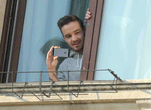 Liam Payne looks at crowds of devoted One Direction fans outside their hotel in Milan, Italy, 12 December 2013