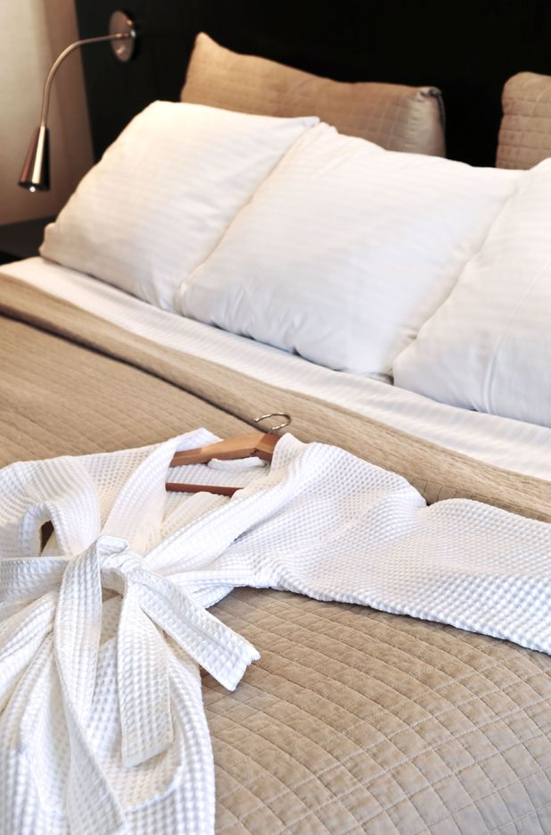 VARIOUS Comfortable bed with clean bathrobe in upscale hotel 2010s