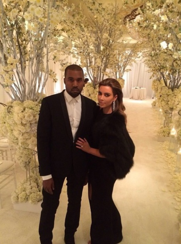 Kim Kardashian and Kanye West pose in black, stand in room filled with flowers - 12.1.2014