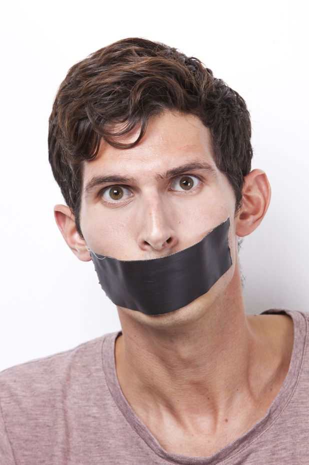Portrait of young man with tape over his mouth staring over white background MODEL RELEASED Portrait of young man with tape over his mouth staring over white background 2012