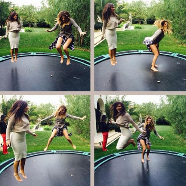 Kim Kardashian and Khloe Kardashian jumping on a trampoline, 4 February 2014