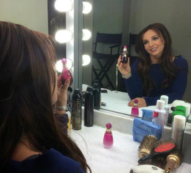 Britney Spears unveils brunette hair while promoting new fragrance.