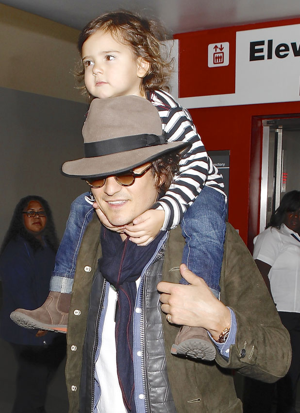 Orlando Bloom carries his son, Flynn on his shoulders as they arrivie on a flight to Los Angeles International Airport (LAX), 19 February 2014