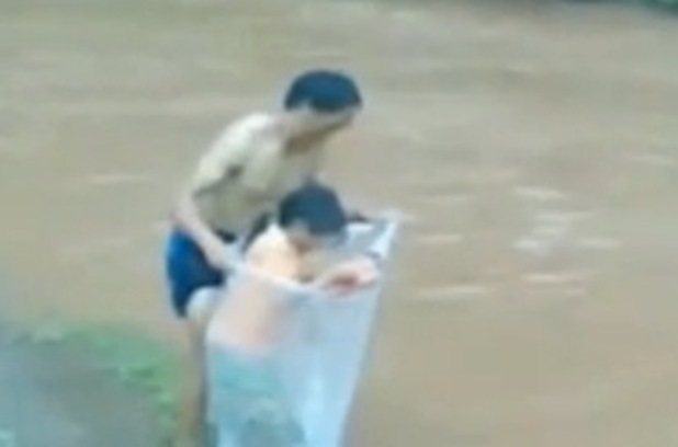 Dad puts child into plastic bag to take them across the river
