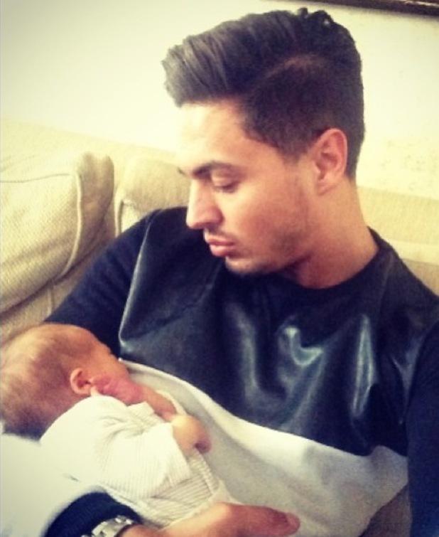 TOWIE's Mario Falcone cuddles baby nephew Buzz. (20 March).