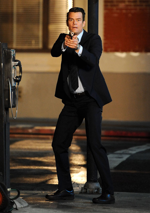 "Josh Duhamel raises his gun at suspects on the set of his new show ""Battle Creek"" filming in Highland Park Ca, March 2014"