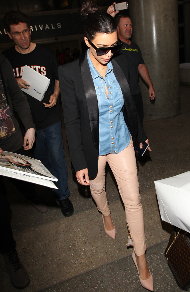 Kim Kardashian arrives in LA on a flight from Paris after checking out her wedding dress, 1 May 2014