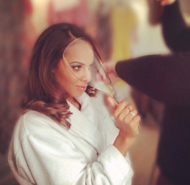 Rochelle Humes holds a face shield in front of her make-up to protect it from hairspray!  7 May 2014