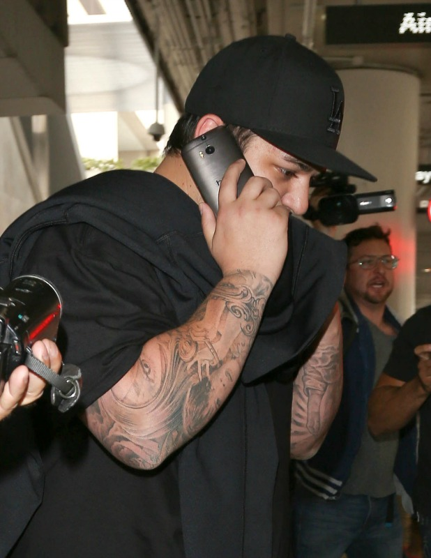Rob Kardashian arrives at Los Angeles International Airport (LAX) and attempts to hide his face as he is escorted to his car. He is reported to have missed sister Kim's wedding in Florence, 24 May 2014