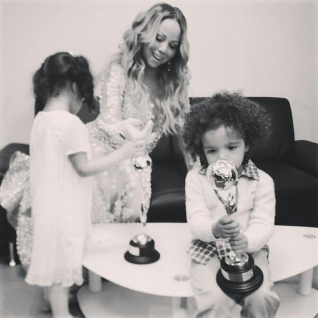 Mariah Carey's twin children Monroe and Moroccan hold her awards backstage at the World Music Awards (27 May).