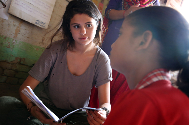 Selena Gomez visits Nepal in her role as UNICEF Ambassador, May 2014.In Nepalgunj, a student shows UNICEF Ambassador, Selena Gomez her school work. As a working adolescent earning additional income for her family, she is happy to receive an education for two hours per day in a UNICEF- supported non-formal classroom setting.