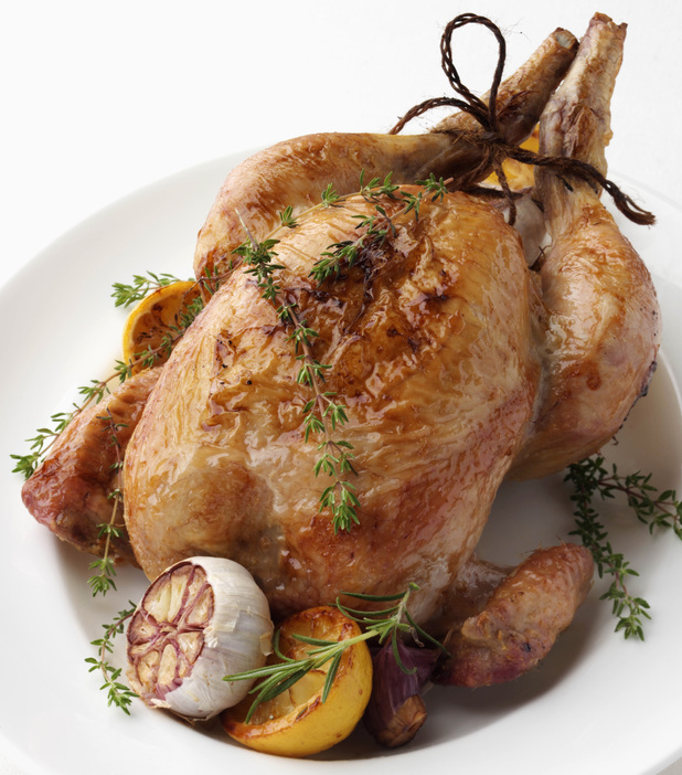 Roast chicken with thyme and garlic head on white background