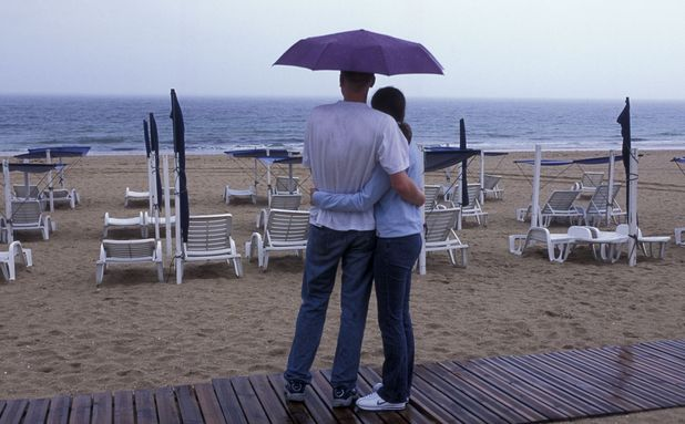 Couple on beach in the rain
