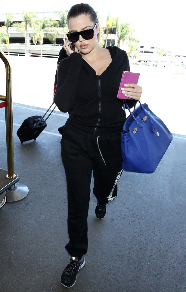 Khloe Kardashian wears tracksuit bottoms and trainers at LAX airport - Los Angeles, America - 13 July 2014