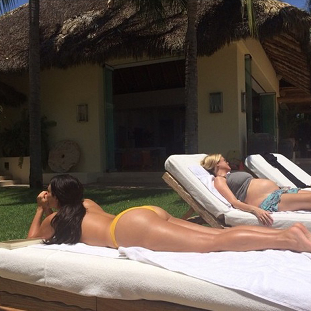 Kim Kardashian shares pictures of herself sunbathing topless in a yellow bikini in Mexico, 17 July 2014