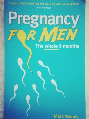 JB Gill reads a book about pregnancy