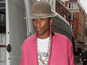 Pharrell Williams wears a bright pink coat - and carries it off!