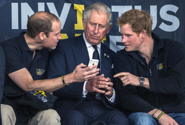 Prince William and Prince Harry share something funny on an iPhone with their father Prince Charles 11 Sep 2014