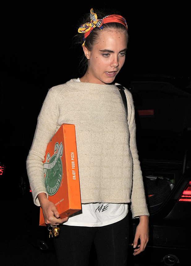 Cara Delevingne wearing a headband, arrives home carrying a takeaway pizza after night out at Chiltern Firehouse, 2014