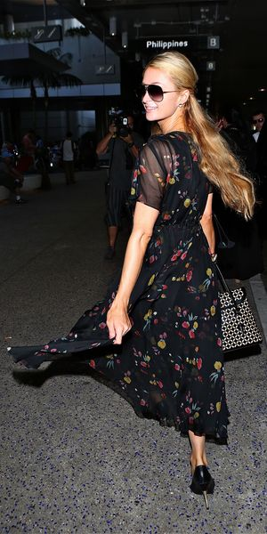Paris Hilton looks happy as she shows off her dress at Los Angeles International Airport (LAX), 3 October 2014