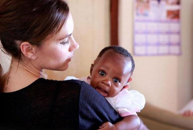 Victoria Beckham cradles a baby during AIDS awareness trip to South Africa - October 2014