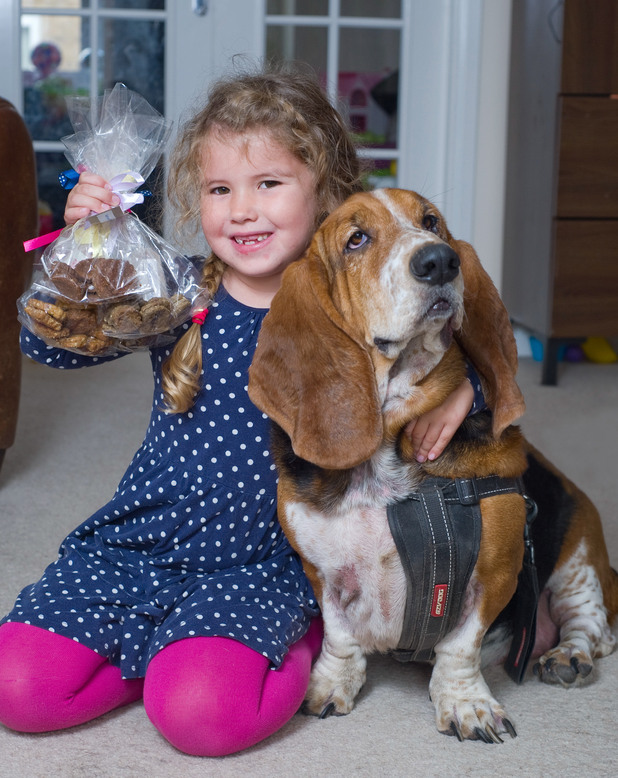 6-year-old Anya Solomon-James with her pet dog Henry and some of her home-made dog biscuits