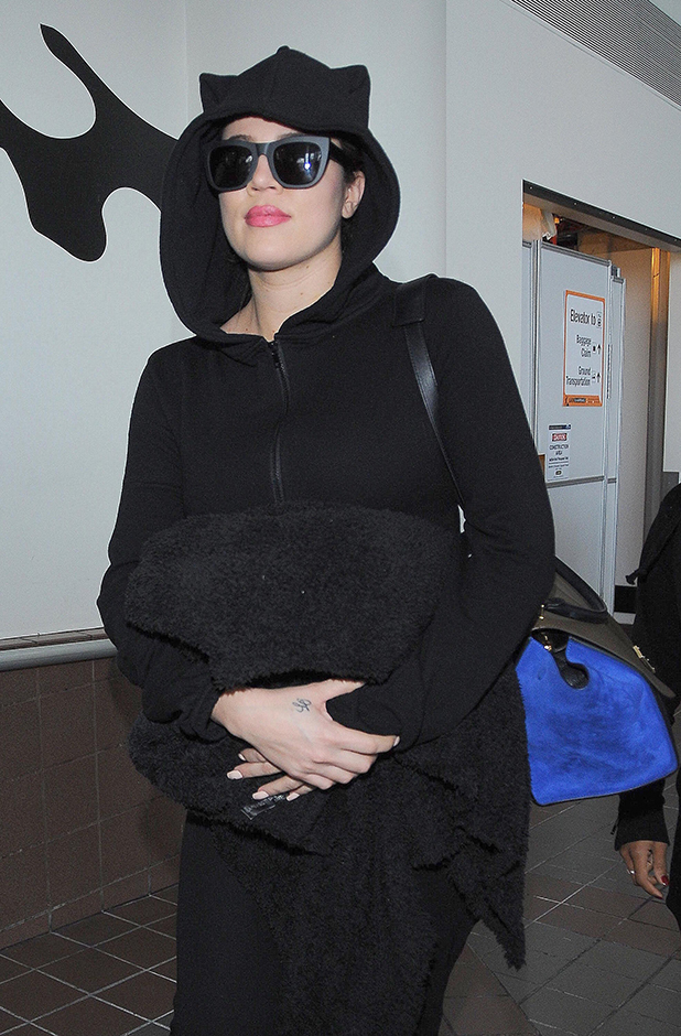 Khloe Kardashian arrives at Los Angeles International Airport (LAX) looking cozy in a hooded black catsuit, 1 November 2014