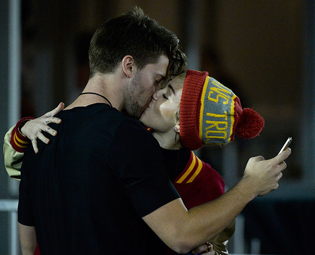 Miley Cyrus (R) kisses Patrick Schwarzenegger during the game between the California Golden Bears and the USC Trojans at Los Angeles Memorial Coliseum on November 13, 2014 in Los Angeles, California. (Photo by Harry How/Getty Images)