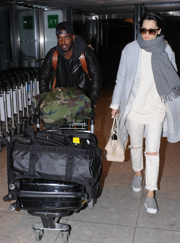 Jessie J hides her face with a scarf while her and her boyfriend Luke James walk through London Heathrow Airport - 26 November.