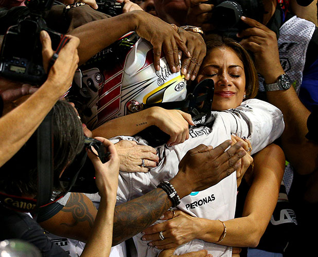 Lewis Hamilton of Mercedes and Great Britain celebrates with his girlfriend Nicole Scherzinger after winning the Formula One World Championship at the Abu Dhabi Formula One Grand Prix,November 23, 2014