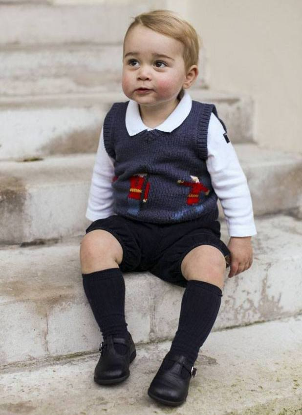 Prince George pictured sitting on the steps of Kensington Palace in official pictures for Christmas, 13 December 2014
