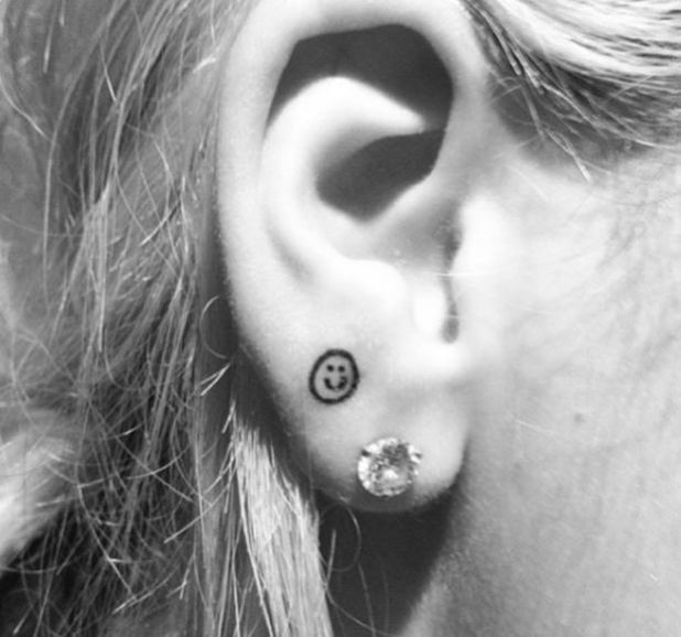 Rita Ora unveils new smiley face tattoo on her ear lobe - 11 January 2015.