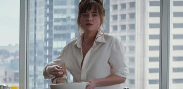 Fifty Shades of Grey new trailer: Jamie Dornan as Christian Grey and Dakota Johnson as Ana Steele. Ana cooking breakfast.