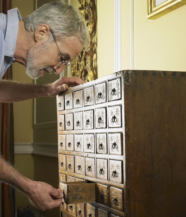 Elderly man looking through cabinet