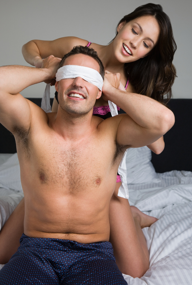 Woman blindfolding man in bed