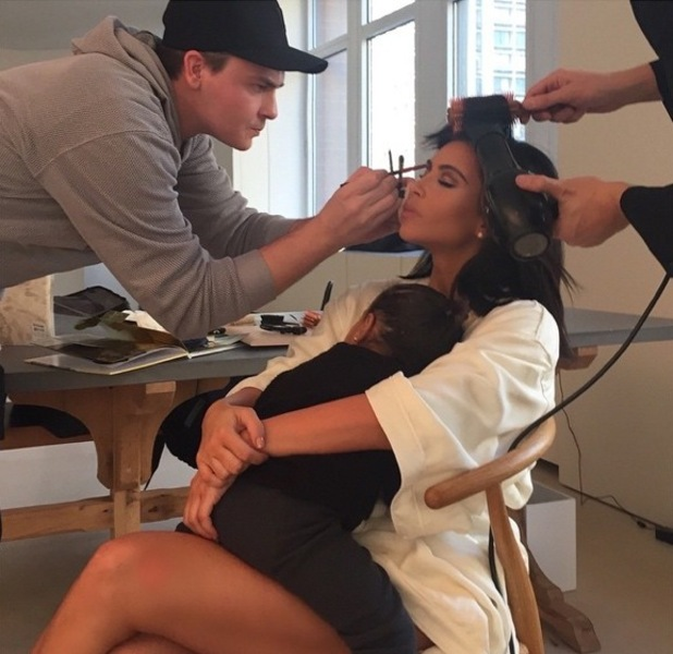Kim Kardashian sits in the make-up chair with Mario Dedivanovic and North West on 10 February 2015