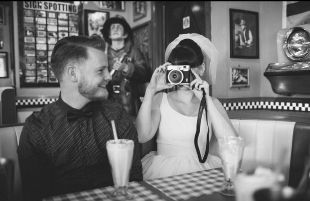 Black and white bride and groom turn camera man on their wedding day